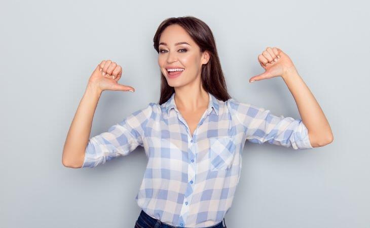 אגואיזם בזוגיות: אישה מחייכת ומצביעה על עצמה