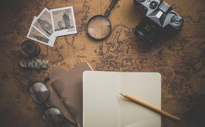 מבחן אישיות - איזה מחזמר מתאים לכם לראות: מפת העולם על שולחן ועליה חפצים שונים