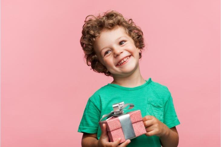 דרכים לעזור לילד להסתגל לאח חדש: ילד מחזיק קופסת מתנה ומחייך