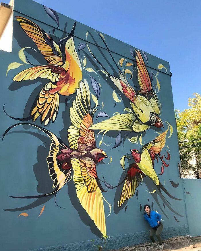 ציורי קיר בגודל מלא של אומנית ארגנטינאית: פיו סילבה ליד קיר עליו ציירה ציפורים במעופן
