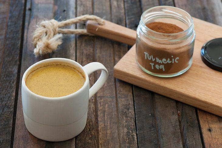 סוגי תה שעוזרים לרדת במשקל: תה כורכום בספל, ולידו צנצנת עם אבקת תה כורכום