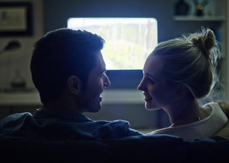 צפייה משותפת בטלוויזיה לחיזוק הזוגיות: גבר ואישה מסתכלים זה על זה על רקע הטלוויזיה