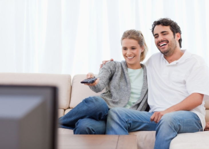 צפייה משותפת בטלוויזיה לחיזוק הזוגיות: זוג צוחק מול הטלוויזיה