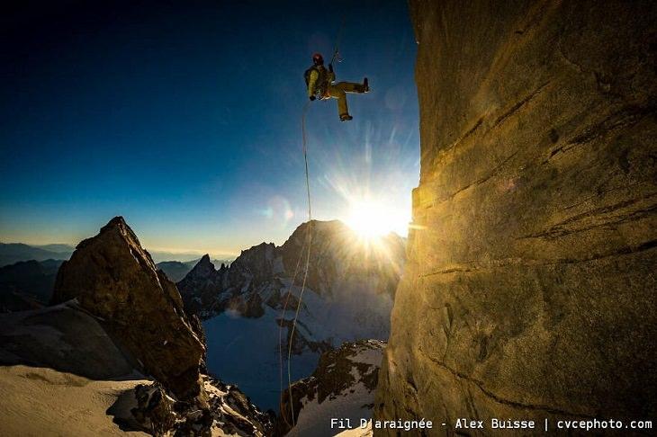 תמונות מתחרות צילום טיפוס הרים: אדם יורד על חבל מהר מול השמש