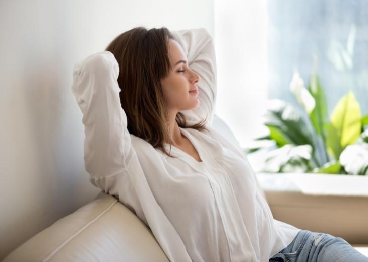 למה אתם צריכים להציב את עצמכם בראש סדר העדיפויות שלכם: אישה יושבת על ספה עם עיניים עצומות