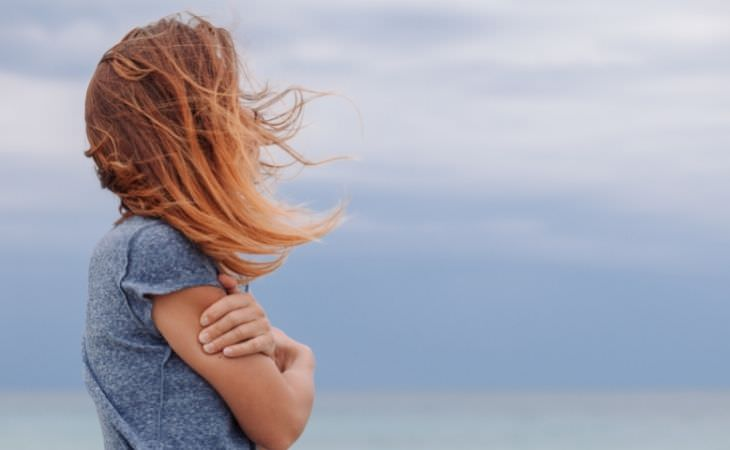 שקרים שהדיכאון מספר לכם: אישה ששערה מסתיר את פניה
