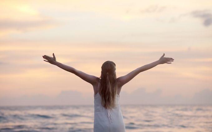 מבחן פילוסופיית חיים ואושר: אישה מרימה ידיים לשמים