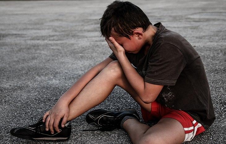 איך לבר עם ילדים על מוות: ילד יושב על כביש ובוכה