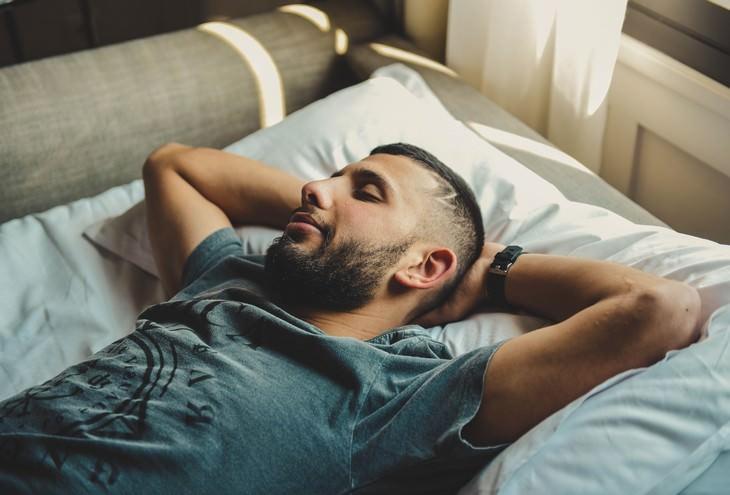 שיטת שינה: גבר ישן על מיטה