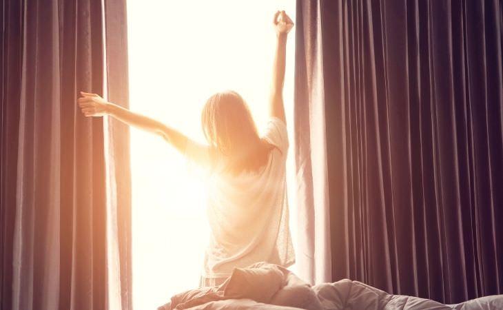 הקשר שבין שעת השינה ודיכאון: אישה מתעוררת מול חלון שטוף שמש