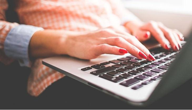 גורמים לנפיחות בידיים ודרכי טיפול בהם: ידי אישה מקלידות על מחשב נייד