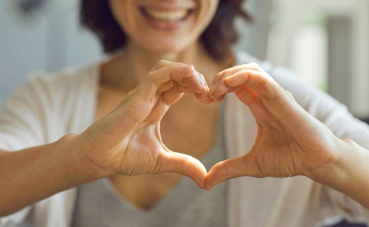 אל תבזבזו זמן על הדברים האלה: אישה מסמלת לב עם הידיים