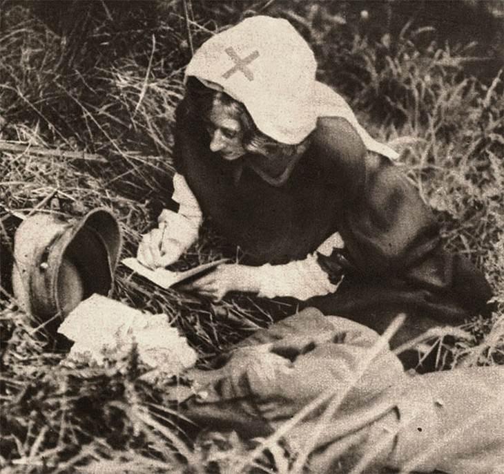 תמונות היסטוריות: אחות מארגון הצלב האדום רושמות את מילותיו האחרונות של חייל פצוע אנושות, 1917.