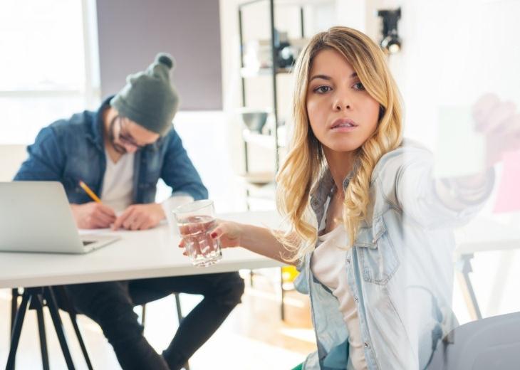 דרכים להפיכת בוקר יום עמוס לרגוע: אישה מסתכלת על פתק בעוד שגבר עובד ברקע