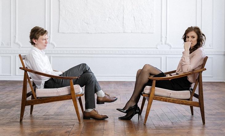 סימני אזהרה לאהבה מזויפת: גבר ואישה לא מרוצים יושבים זה מול זו
