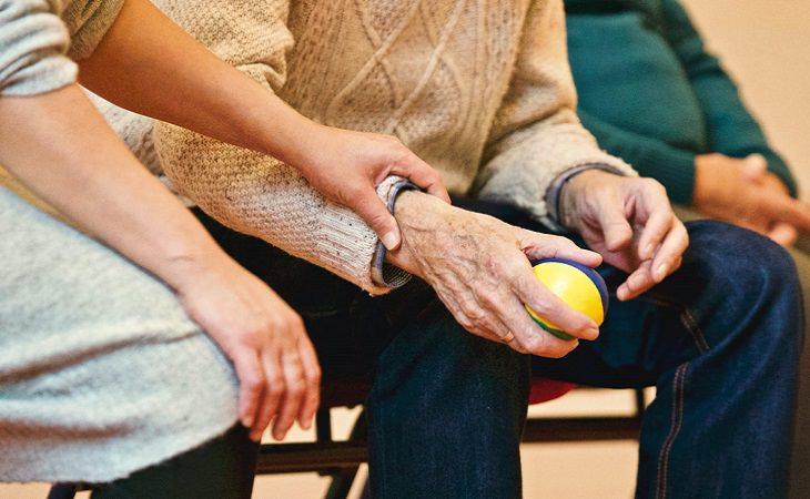 תביעת ביטוחי סיעודי: ידיים מבוגרות אוחזות בכדור קטן