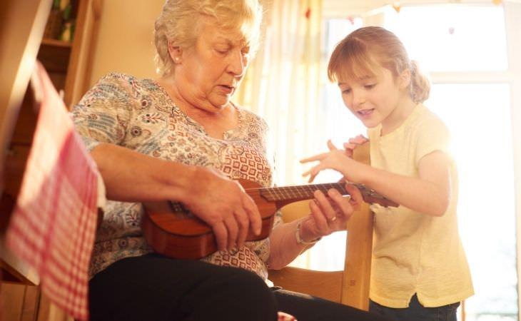 איך ללמוד יכולות חדשות בגיל מבוגר: ילדה מלמדת סבתא איך לנגן בגיטרה
