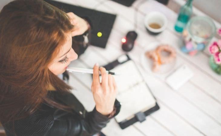 איך ללמוד יכולות חדשות בגיל מבוגר: אישה חושבת עם עט ביד