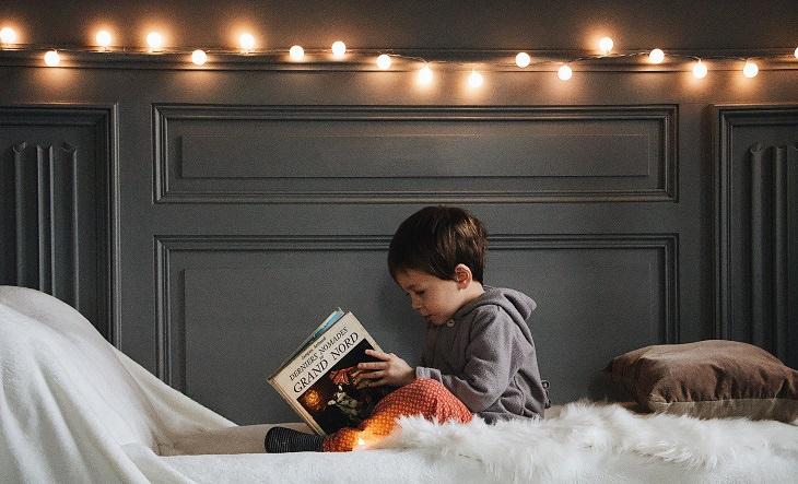 מחקר על הצלחה של ילדים: ילד קורא ספר במיטה