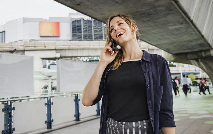 שינויים קטנים לחיים מאושרים: אישה שמחה מדברת בטלפון