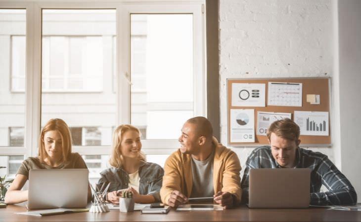 יתרונות שבוע של 4 ימי עבודה: אנשים עובדים מול שולחן