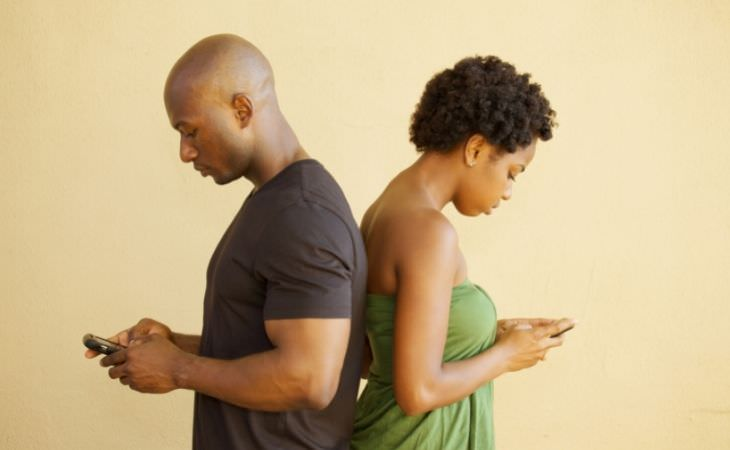 מה לעשות כשמתוסכלים בזוגיות: זוג עם הגב אחד לשני משתמשים בסמארטפון