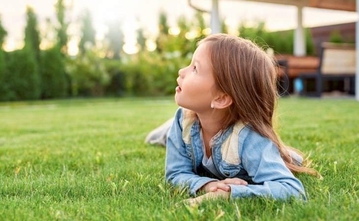 למה חשוב שילדים ישחקו לבד בחוץ: ילדה שוכבת על הדשא