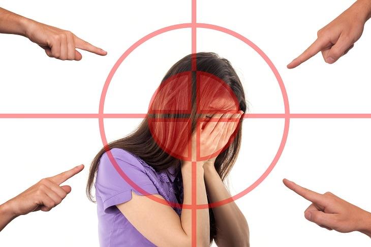 טריקים שהמוח שלכם עושה לכם: ילדה מחזיקה את הראש בידיה וכוונת ואצבעות מכוונות עליה