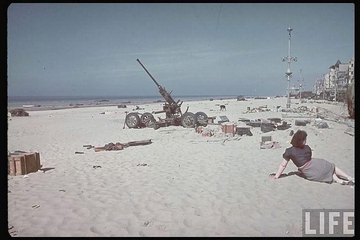 תמונות היסטוריות מרתקות: אישה נחה על החוף לצד ציוד של בעלות הברית שנשאר מאחור לאחר פינוי דנקרק - 1940.