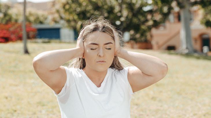 תסמינים מוקדמים של מיגרנה: אישה אוחזת בראשה