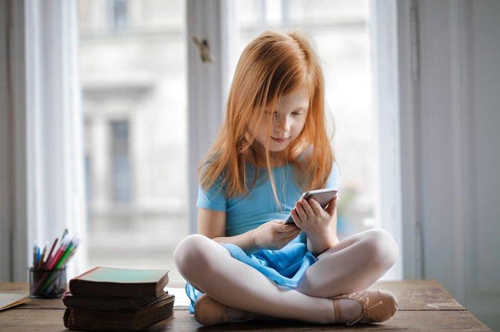 איך לבחור סמארטפון לילד: ילדה עם סמארטפון