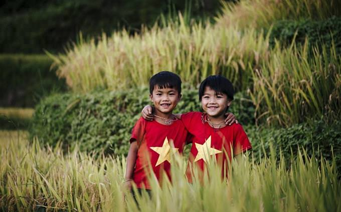 """חידון טריוויה """"מי בראש"""": זוג ילדים וייטנאמים לבושים בחולצה עם דגל וייטנאם"""