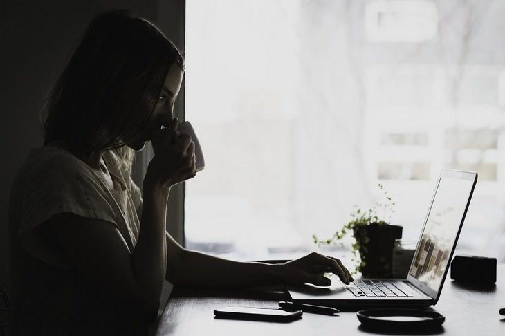 השפעת חיסון הקורונה על נשים הרות ומניקות: אישה עובדת על המחשב ושותה