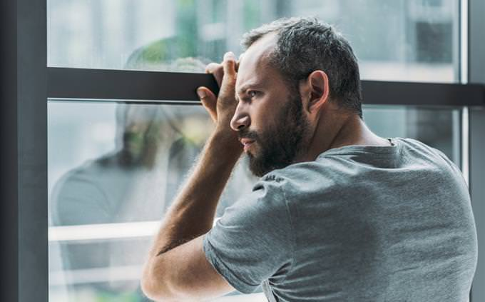 מבחן מערכת יחסים פנימית: גבר מהורהר נשען על חלון