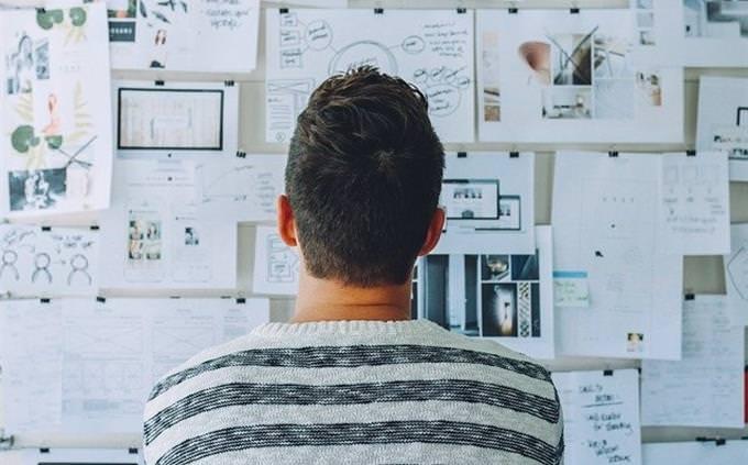 שאלון אישיות - איזה יזם אתה: אדם מסתכל על לוח מלא בדפים