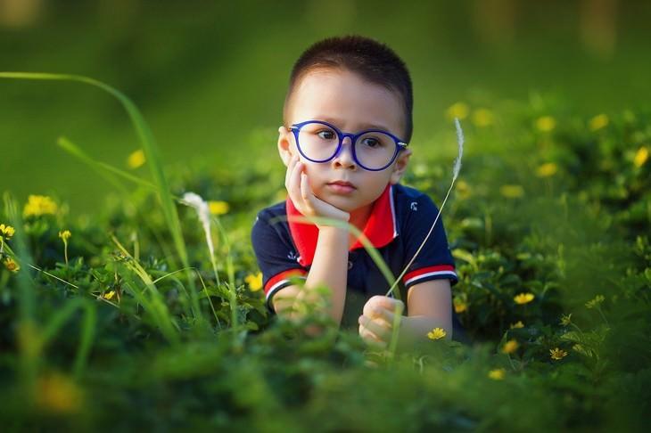 ילדים ונימוסים: ילד עם משקפיים שוכב על הדשא