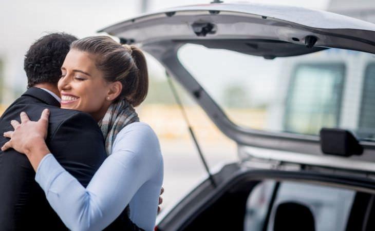 איך להגיב לחדשות דרמטיות של הילדים: אישה מחבקת גבר לצד רכב עם תא מטען פתוח