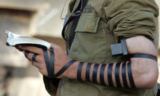 אוסף כתבות בנושאי יהדות: תפילין מונחות על זרוע של חייל מתפלל