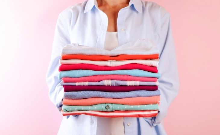 איך לנקות עם אקונומיקה: אישה מחזיקה בגדים צבעוניים מקופלים