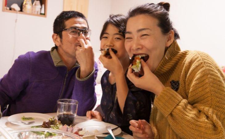 מנהגים חברתיים של אנשים שחיים שנים רבות: משפחה אסייתית אוכלת יחדיו