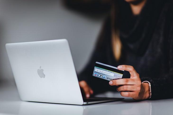 שירות של בנק ישראל - מעבר מקוון מבנק לבנק: אישה מחזיקה כרטיס אשראי מול המחשב