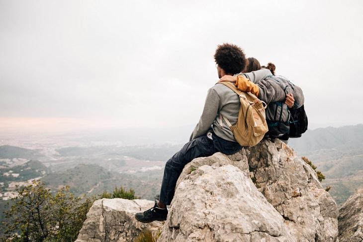 טיול אחרי צבא בעידן פוסט קורונה: גבר ואישה יושבים חבוקים על סלע על הר