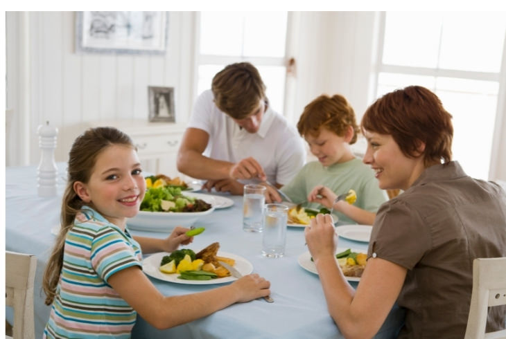 יתרונות ארוחות משפחתיות משותפות: ילדה מחייכת בזמן ארוחה משפחתית עם הוריה ואחיה