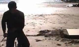 אמן יוצר כיסא ביציקת מתכת בחוף הים