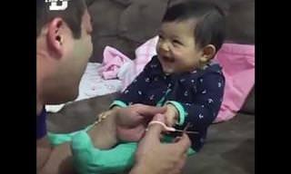 אב מנסה לגזור לביתו הפעוטה ציפורניים - ולא מצליח מרוב צחוק
