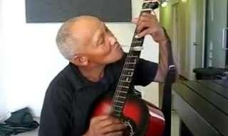איש פורט על גיטרה עם כפית